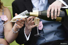 FILE - Racegoers pouring champagne.