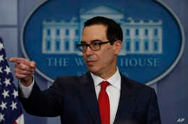 Treasury Secretary Steven Mnuchin points to a reporter to take a question during the news briefing at the White House, in Washington, Aug. 25, 2017.