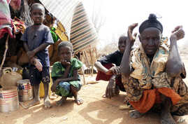 FILE - Refugees sit outside in an open area as there is lack of tents at the Dollo Ado refugee camp, Ethiopia.