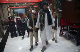 In this photo taken July 25, 2017, Mohammed Naseer, with black turban, holds his sons' hand when they enter a Pizza Restaurant in Kabul, Afghanistan. Mohammed Naseer spent several weeks arranging for his son, a nephew and several other children from
