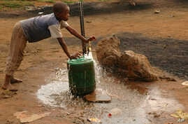 FILE - A child fills a container with water for domestic use in Delmas, east of Johannesburg, South Africa.