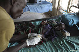 An UPDF medic takes care of a malnourished child with malaria in a hospital in Bor March 15, 2014.