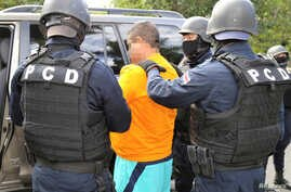 FILE - Officers of the National Intelligence and Security police arrest an alleged drug trafficker in San Jose, Costa Rica, Nov. 22, 2016.