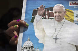 A churchgoer holds a copy of the Catholic Mirror newspaper showing a photograph of Pope Francis, after mass outside the Holy Family Minor Basilica in downtown Nairobi, Kenya, Nov. 22, 2015.