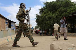 FILE - A Somali soldier patrols a street following a suicide car bomb and gun attack in Afgoye, Somalia, Oct. 19, 2016.