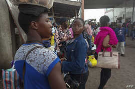 Residents from the western region in Cameroon arrive at the bus terminal in Buea following renewed clashes in the area on July 15, 2018.