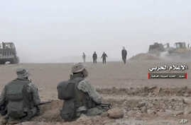 This frame grab from video provided Wednesday, Nov 8, 2017 by the government-controlled Syrian Central Military Media, shows Syrian pro-government troops taking up positions during fighting with insurgents on the Iraq-Syria border. The Britain-based