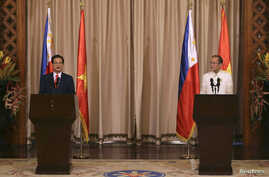 Vietnam's Prime Minister Nguyen Tan Dung (L) talks next to Philippines' President Benigno Aquino during a joint news conference at the Malacanang Presidential Palace in Manila, May 21, 2014.
