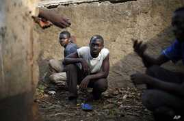 Men take cover in a toilet as heavy gunfire erupts in the Miskin district of Bangui, Central African Republic, Monday Feb. 3, 2014. In what a French soldier on the scene described as the heaviest exchange of fire he'd seen since early December 2013,