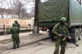 Soldiers without insignia guard buildings in the Crimean capital, a day after the Ukrainian prime minister called for Russian help, Simferopol, Ukraine, March 2, 2014. (Elizabeth Arrott/VOA).