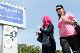 Women walk past a poster of the play ?Made in Tunisia, 100 percent halal? by Tunisian actor, playwright Lotfi Abdeli. The play was boycotted previously by hundreds of Salafi Muslims who believed the show was offensive to Islam, (File Photo).
