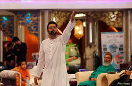 FILE - Aamir Liaquat Hussain gestures during a live show in Karachi, Pakistan, July 26, 2013.