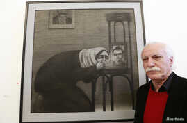 Syrian artist Youssef Abdelke stands near his artwork during an exhibition at a gallery in Beirut, Jan. 6, 2014.