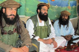 FILE - Pakistani Taliban spokesman Shahidullah Shahid, center, flanked by bodyguards, talks to reporters at undisclosed location, Pakistani tribal area of Waziristan, Oct. 5, 2013.