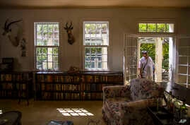 FILE - A visitor peers into the living room at Finca Vigia, home of the late U.S. literary icon Ernest Hemingway in Havana, Cuba, June 15, 2016.