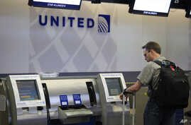 FILE - A man uses a United Airlines check-in kiosk at San Francisco International Airport in San Francisco.