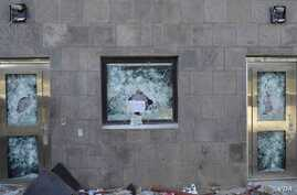 """""""Anything but the messenger of God,"""" reads a sign left in the shattered window of a U.S. compound after it was stormed by rioters in Sana'a, Yemen, Sept. 13, 2012."""