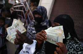 FILE - Women display paper currency after they received it from the U.N. children's agency in Sanaa, Yemen, Nov. 14, 2015.