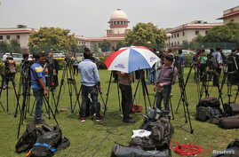 Television journalists are seen outside the Supreme Court building in New Delhi, India, August 22, 2017.