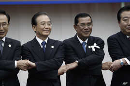From left: South Korea's President Lee Myung-bak, China's Premier Wen Jiabao, Cambodia's Prime Minister Hun Sen and Japan's Prime Minister Yoshihiko Noda hold hands together during the ASEAN Plus Three (APT) Commemorative Summit in Phnom Penh, Cambod...