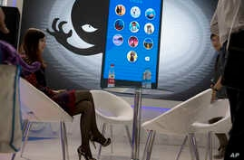 A woman sits near a display showing the dangers of hackers breaking into mobile devices during the Global Mobile Internet Conference in Beijing, China, April 29, 2016.