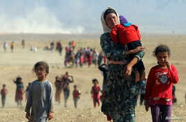 Displaced people from the minority Yazidi sect, fleeing violence from forces loyal to the Islamic State in Sinjar town, walk towards the Syrian border on the outskirts of Sinjar mountain near the Syrian border town of Elierbeh of Al-Hasakah Governora