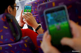 """Passengers play the augmented reality mobile game """"Pokemon Go"""" by Nintendo inside a bus in Hong Kong, China, Aug. 12, 2016."""