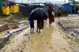 People walk after a storm at Balukhali refugee camp in Cox's Bazar, Bangladesh June 10, 2018, in this image obtained from social media. (K. Marton/Save the Children/via Reuters)