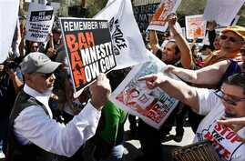 An anti-immigration rights protester, left, holds up a sign as he is pointed at and shouted at by immigration rights marchers during a Puente Movement event March Against Deportation, Family Separation, and Workplace Raids on March 11, 2013, in Phoen
