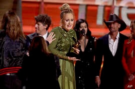 """Adele accepts the award for album of the year for """"25"""" at the 59th annual Grammy Awards, Feb. 12, 2017."""