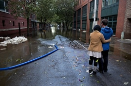 Steve Brett and his wife, Toi Brett, of Hoboken, N.J., look down First Street at high water near their home in Hoboken, N.J., Oct. 31, 2012, in the wake of superstorm Sandy.