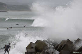 Waves crash as Typhoon Vongfong approaches Japan's main islands while surfers try to ride  a wave at Eguchihama Beach in Hioki, Kagoshima prefecture, Oct. 12, 2014.
