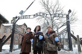 FILE - Holocaust survivors walk outside the gate of the Auschwitz Nazi death camp in Oswiecim, Poland, Jan. 27, 2015.