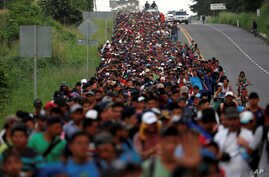 Migrants, part of a caravan traveling from Central America toward the United States, walk on a road that links Ciudad Hidalgo with Tapachula, Mexico, Nov. 2, 2018.