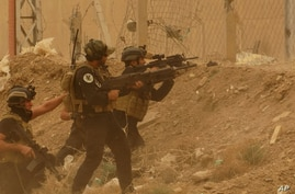 Security forces defend their headquarters against attacks by Islamic State extremists during sand storm in the eastern part of Ramadi, the capital of Anbar province, Iraq, May 14, 2015.