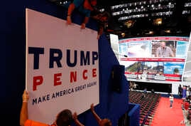 Workers place a sign as they prepare at Quicken Loans Arena for the Republican National Convention, Sunday, July 17, 2016.