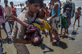 A man shakes a Rohingya Muslim boy while trying to revive him after the boat he was traveling in capsized just before reaching shore at Shah Porir Dwip, Bangladesh, Thursday, Sept. 14, 2017. Nearly three weeks into a mass exodus of Rohingya fleeing v...