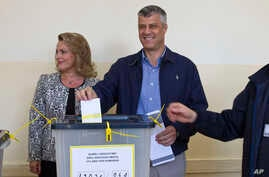 Kosovo Prime Minister Hashim Thaci, joined by his wife Lumnije casts his vote at a polling station in Pristina, Nov 3, 2013.