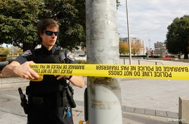 A police officer closes off the scene near the Canada War Memorial following a shooting incident in Ottawa, Oct. 22, 2014.