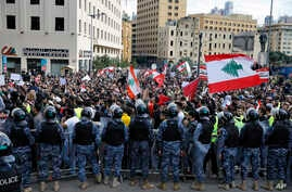 Anti-government protesters hold Lebanese flags and chant slogans as riot police stand guard in front of the government building, in central Beirut, Lebanon, Dec. 23, 2018.