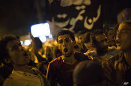 """Supporters of Egypt's ousted President Mohammed Morsi chants slogans against the Egyptian Army after """"Iftar"""" during a protest near Cairo University in Giza, Egypt, Aug. 4, 2013."""