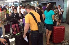 Passengers stand with their luggage outside Terminal 5 at London's Heathrow airport after flights were canceled due to a British Airways IT systems failure, May 27, 2017.