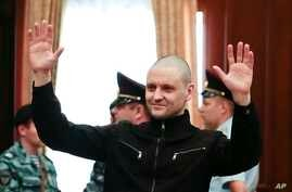 Russian opposition activist Sergei Udaltsov waves in a court room prior to a hearing in the Bolotnaya Square protest trial in Moscow, July 24, 2014.