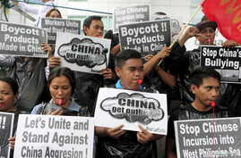 Protesters from the Socialista National Confederation of Labor activist group blow whistles as a part of the noise barrage during a rally over the South China Sea disputes with China, outside the Chinese Consulate in Makati City, Manila, July 10, 201