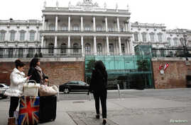 People pass by Palais Coburg hotel where nuclear talks are taking place in Vienna, Feb. 19, 2014.