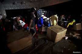 People carry looted goods as they walk through a flooded street in Acapulco, Sept. 18, 2013.
