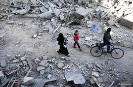 People walk on the rubble of damaged buildings at a site hit yesterday by airstrikes in the rebel held Douma neighborhood of Damascus, Syria, Nov. 18, 2016.