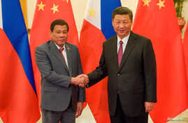 FILE - Chinese President Xi Jinping, right, shakes hands with Philippines President Rodrigo Duterte before their bilateral meeting during the Belt and Road Forum, Beijing, May 15, 2017.