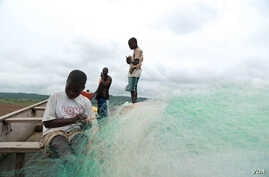 Here child slaves nervously prepare a fishing net under the watchful eye of a fisherman.