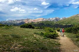 Hikers enjoy the Ute Trail, taking in the view of the alpine tundra and Never Summer Mountains.